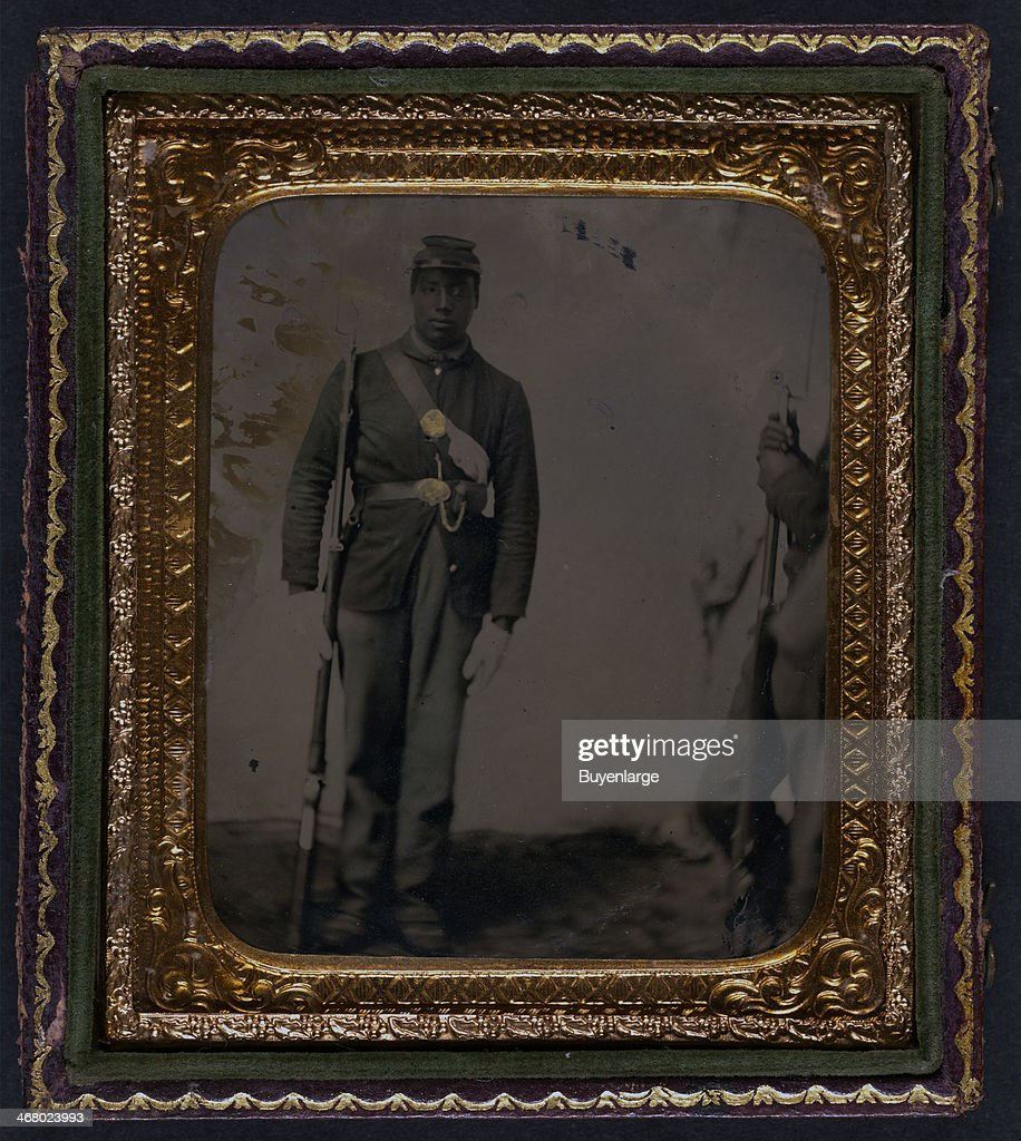 Daguerreotype of an AfricanAmerican soldier in Union uniform and gloves with musket 1863 Another soldier is visible waiting at the side