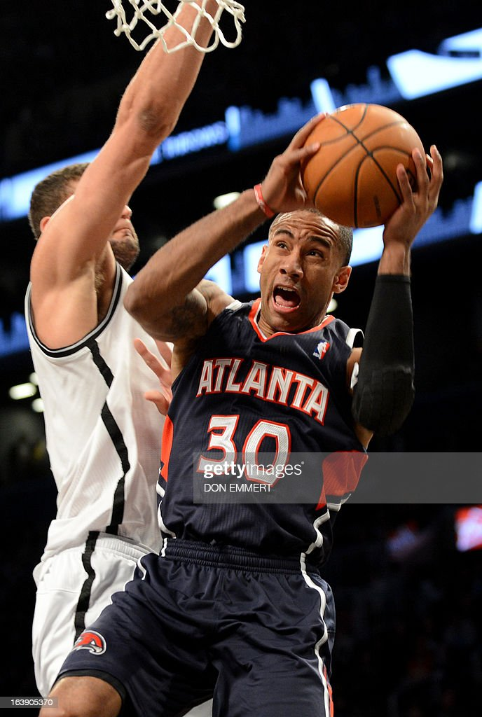 Dahntay Jones (R) of the Atlanta Hawks gets a shot off past Brooklyn Nets Brook Lopez March 17, 2013 at the Barclay Center in New York.