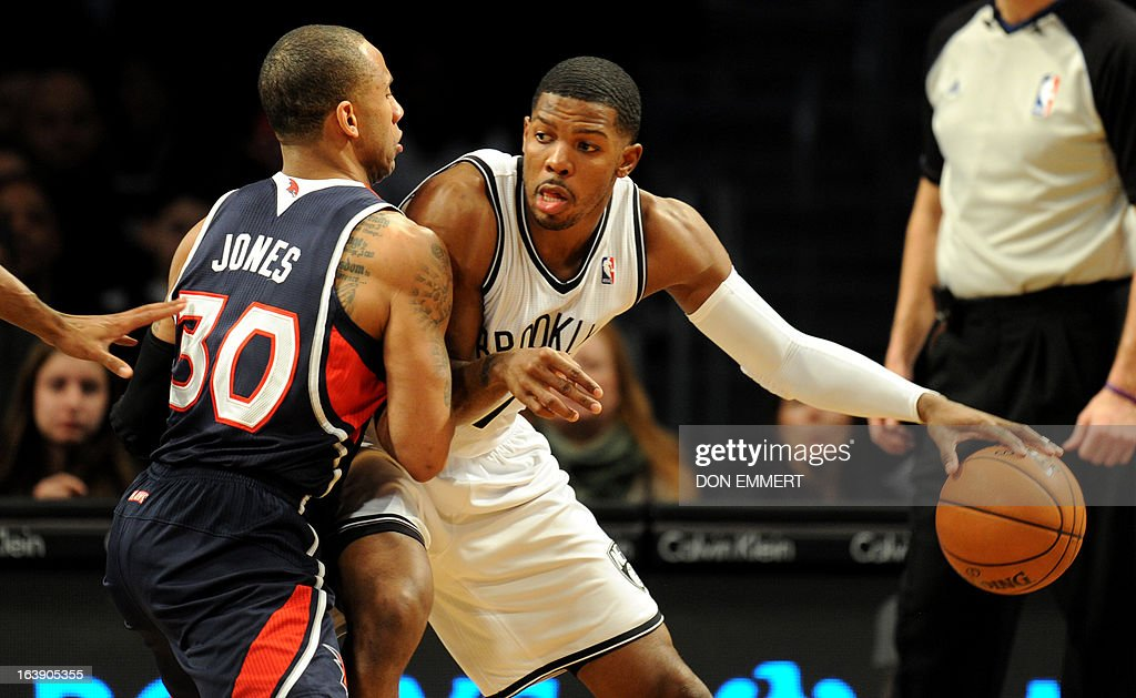 Dahntay Jones (L) of the Atlanta Hawks guards Brooklyn Nets Joe Johnson March 17, 2013 at the Barclay Center in New York.