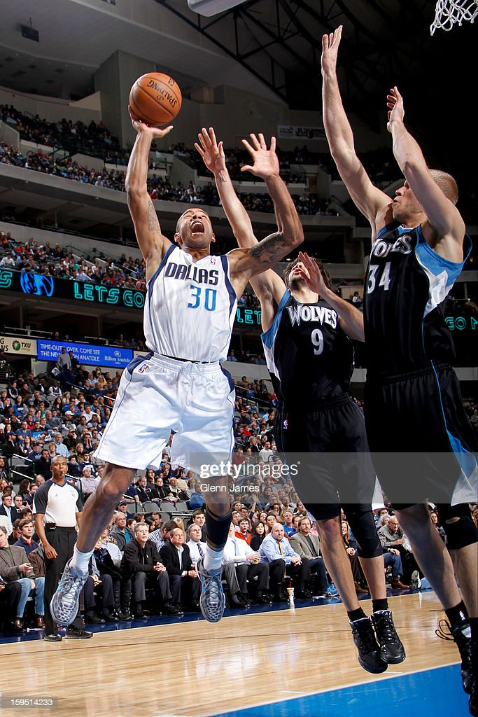 Dahntay Jones #30 of the Dallas Mavericks drives to the basket against Ricky Rubio #9 and Greg Stiemsma #34 of the Minnesota Timberwolves on January 14, 2013 at the American Airlines Center in Dallas, Texas.