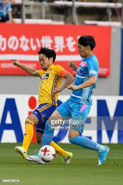 Daichi Kamada of Sagan Tosu and Shingo Tomita of Vegalta Sendai compete for the ball during the JLeague J1 match between Sagan Tosu and Vegalta...