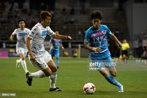 Daichi Kamada of Sagan Tosu and Tomonobu Yokoyama of Consadole Sapporo compete for the ball during the JLeague J1 match between Sagan Tosu and...