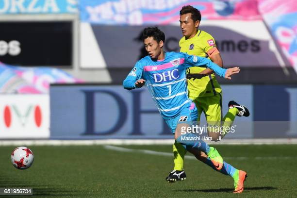 Daichi Kamada of Sagan Tosu and Toshihiro Aoyama of Sanfrecce Hiroshima compete for the ball during the JLeague J1 match between Sagan Tosu and...