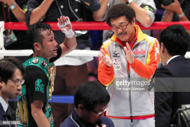 Daigo Higa of Japan celebrates retaining his title with his trainer and former champion Yoko Gushiken after beating Thomas Masson of France in the...