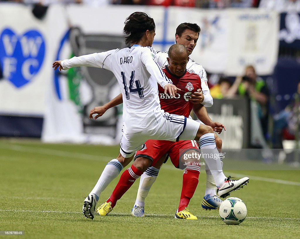 Daigo Kobayashi #14 and Alain Rochet #4 of the Vancouver Whitecaps FC defend against <a gi-track='captionPersonalityLinkClicked' href=/galleries/search?phrase=Robert+Earnshaw&family=editorial&specificpeople=208190 ng-click='$event.stopPropagation()'>Robert Earnshaw</a> #10 of the Toronto FC during their MLS game at BC Place March 2, 2013 in Vancouver, British Columbia, Canada.