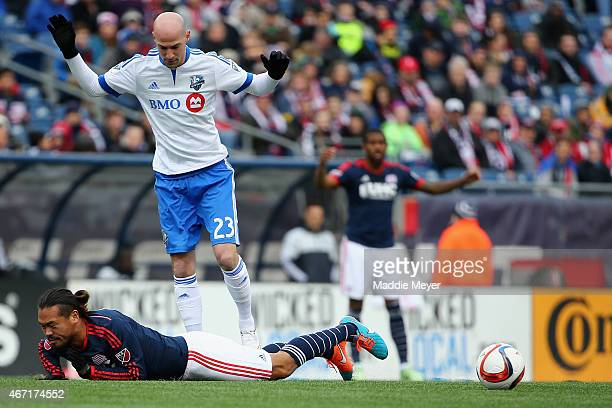 Daigo Kobayashi of New England Revolution gets tripped up on Laurent Ciman of Montreal Impact during the second half at Gillette Stadium on March 21...