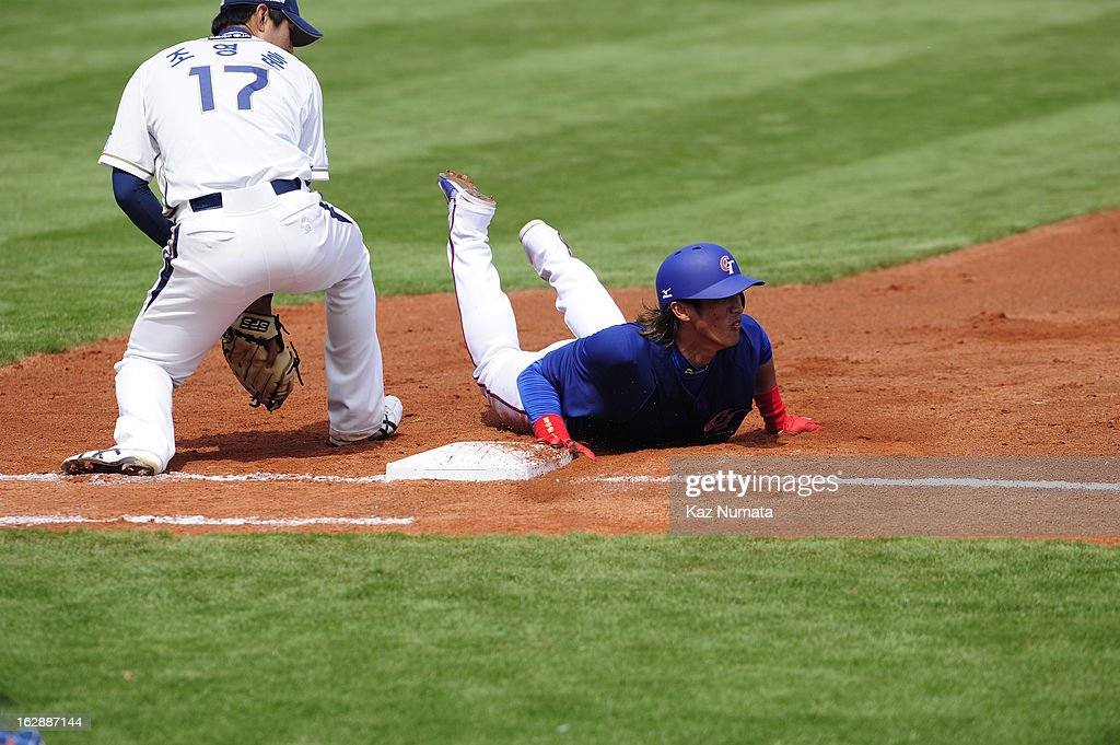 Dai-Kang Yang #1 of Team Chinese Taipei dives back to first base during the World Baseball Classic exhibition game against the NC Dinos at Taichung Intercontinental Baseball Stadium on Thursday, February 28, 2013 in Taichung, Tawain.