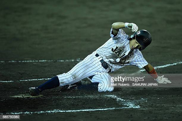 Daiki Kondo of Japan slides safely to home plate in the bottom half of the sixth inning in the super round game between Japan and Venezuela during...