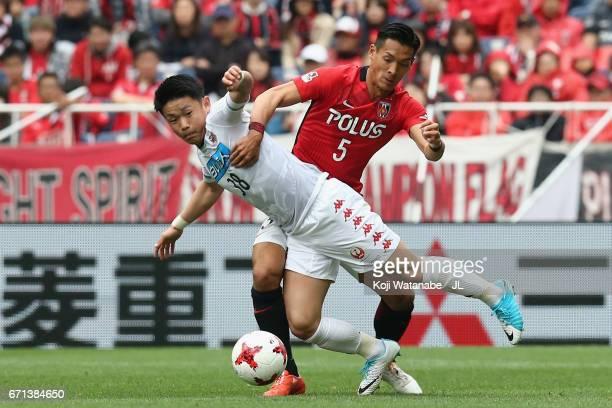 Daiki Suga of Consadole Sapporo is challenged by Tomoaki Makino of Urawa Red Diamonds during the JLeague J1 match between Urawa Red Diamonds and...