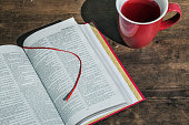 English Bible, red cup of tee on a wooden table