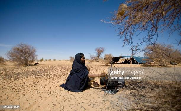 Daily life in Ada's camp near Essouk Her sister is pictured preparing a meal Ada is one of the pregnant nomadic women who is about to give birth and...