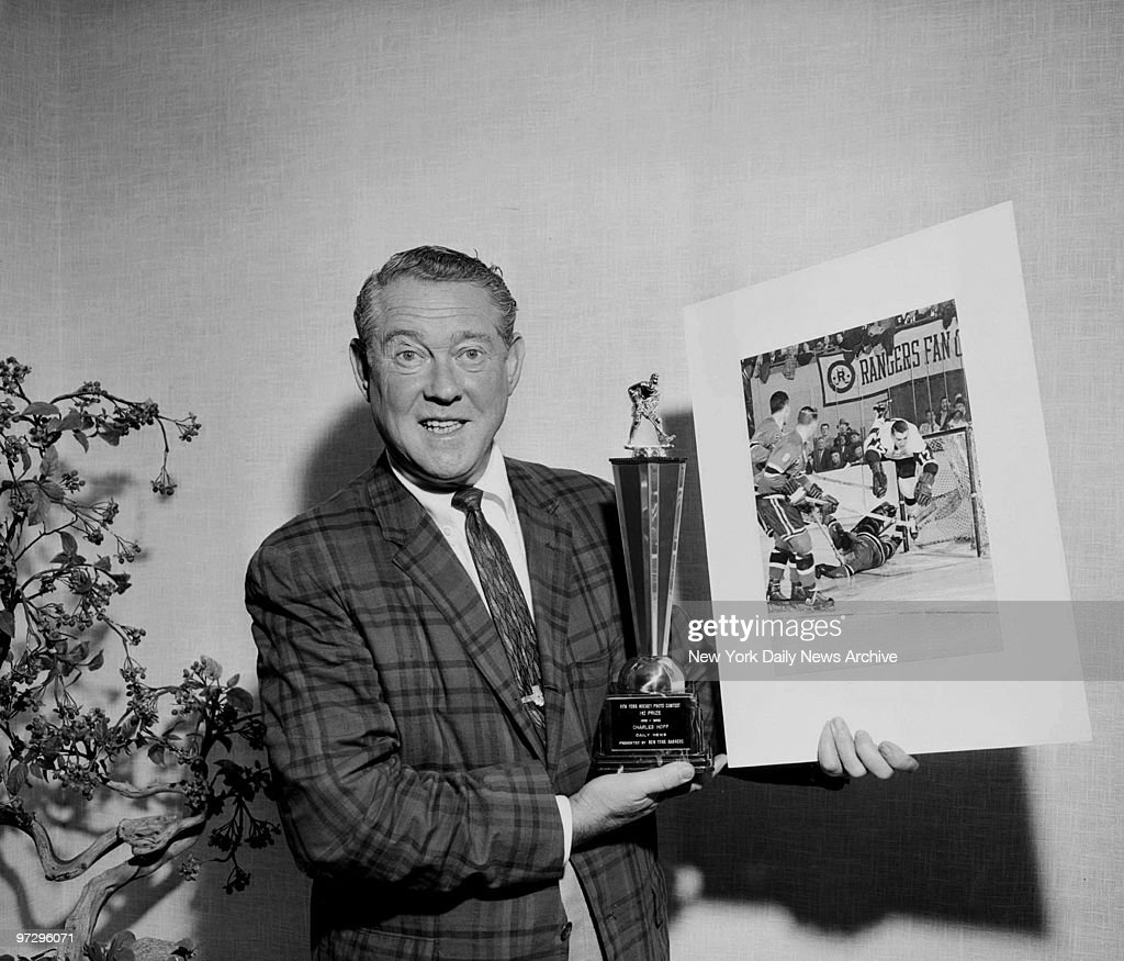 Daily News photographer Charles Hoff holding hockey award trophy and the photo for which he won. Photo shows Ranger goalie Gump Worsley making a save aginst Detroit Red Wing Claude LaForge.,