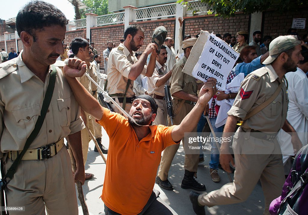 A daily wage employee holds a noose around his neck as Indian policemen try to disperse the crowd during a protest against the government on August 21, 2014 in Srinagar, the summer capital of Indian administered Kashmir, India. Indian police used water canons and batons to disperse dozens of daily wage employees protesting and demanding regulation of their services and a hike in monthly wages.