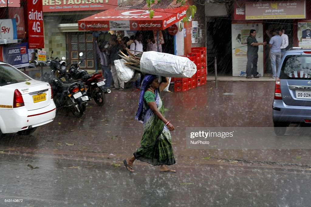 A daily wage laborer carries fire woods atop her head as she walks back home wade through in the monsoon rain in the eastern Indian city Bhubaneswar, India, Sunday, 26 June 2016.