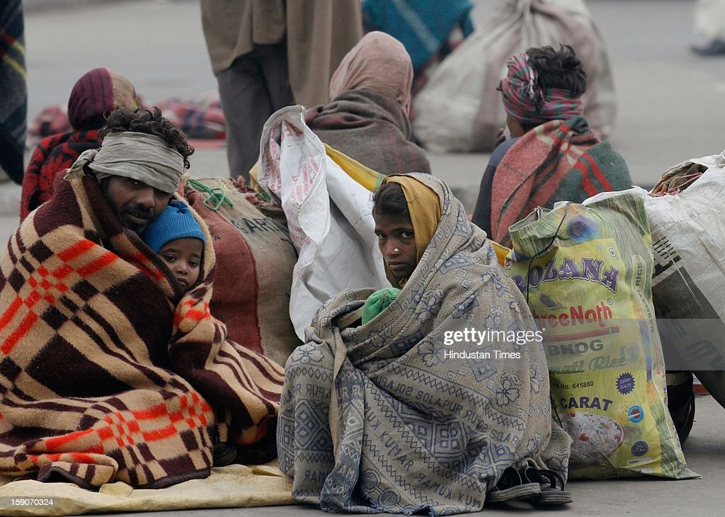 Daily wage laborer from Madhya Pradesh wrap themselves in blanket to brave one of the coldest morning near Sarai Kale Khan bus terminal on January 7, 2013 in New Delhi, India. Dense fog and icy winds disrupted normal life as Delhi's minimum temperature settled at five notches below average at 2.4 degrees Celsius. Fog forced visibility to drop to about 500 metres in the morning resulting in 15 flights and 42 trains were delayed out of Delhi while 18 trains got cancelled.