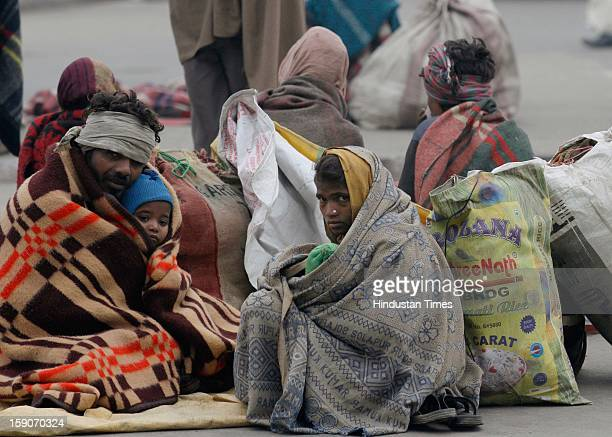 Daily wage laborer from Madhya Pradesh wrap themselves in blanket to brave one of the coldest morning near Sarai Kale Khan bus terminal on January 7...