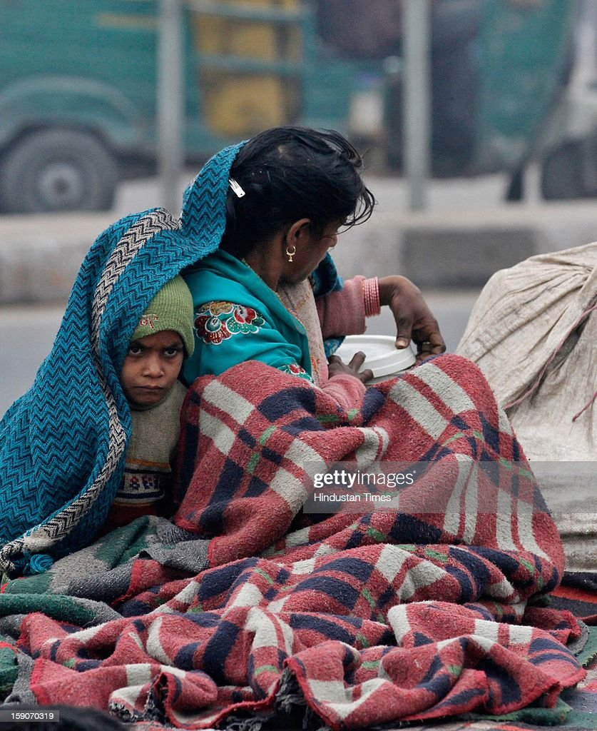 Daily wage laborer lady from Madhya Pradesh with her child wrapped in blanket to brave one of the coldest morning near Sarai Kale Khan bus terminal on January 7, 2013 in New Delhi, India. Dense fog and icy winds disrupted normal life as Delhi's minimum temperature settled at five notches below average at 2.4 degrees Celsius. Fog forced visibility to drop to about 500 metres in the morning resulting in 15 flights and 42 trains were delayed out of Delhi while 18 trains got cancelled.