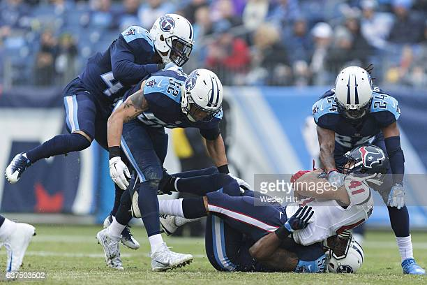 Daimion Stafford and Avery Williamson of the Tennessee Titans tackle Jonathan Grimes of the Houston Texans at Nissan Stadium on January 1 2017 in...