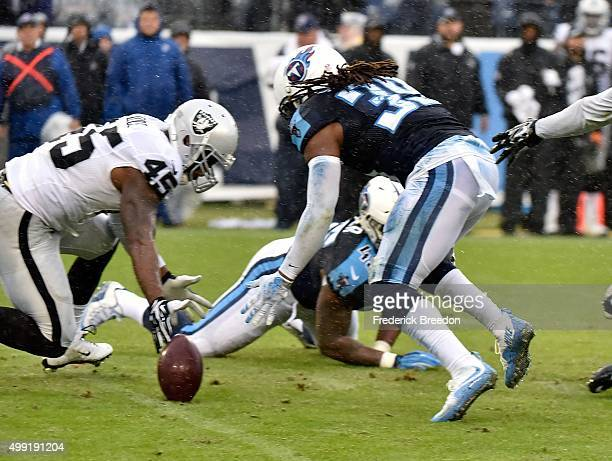 Daimion Stafford of the Tennessee Titans and Marcel Reece of the Oakland Raiders fight for a ball after a fumble on a kickoff during the second half...