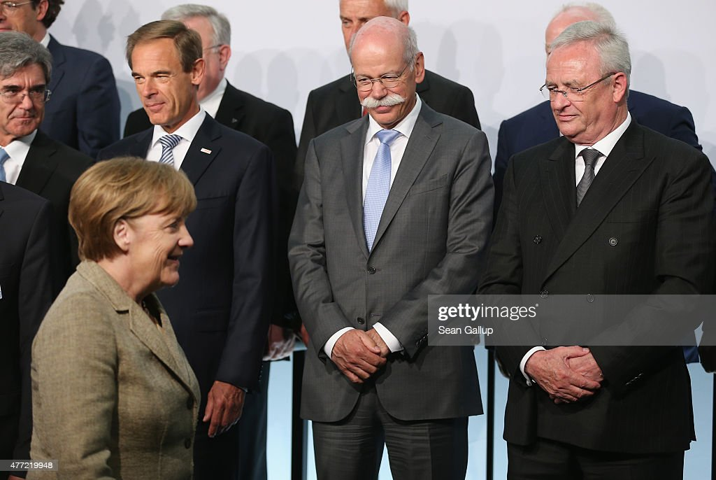 Daimler AG CEO <a gi-track='captionPersonalityLinkClicked' href=/galleries/search?phrase=Dieter+Zetsche&family=editorial&specificpeople=241297 ng-click='$event.stopPropagation()'>Dieter Zetsche</a> (C) and Volkswagen Group CEO <a gi-track='captionPersonalityLinkClicked' href=/galleries/search?phrase=Martin+Winterkorn&family=editorial&specificpeople=840091 ng-click='$event.stopPropagation()'>Martin Winterkorn</a> (R) look on as German Chancellor <a gi-track='captionPersonalityLinkClicked' href=/galleries/search?phrase=Angela+Merkel&family=editorial&specificpeople=202161 ng-click='$event.stopPropagation()'>Angela Merkel</a> arrives at the government-sponsored electro-mobility conference on June 15, 2015 in Berlin, Germany. Top representatives of German and industry and government officials are meeting to discuss the future of electric-powered transport in Germany.