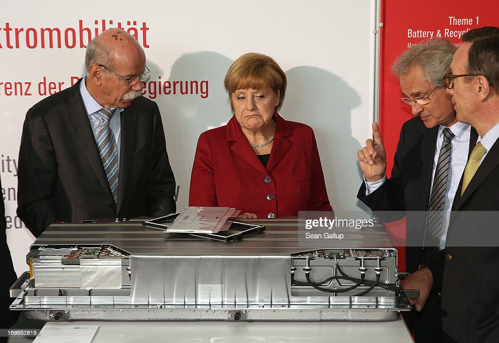 Daimler AG head Dieter Zetsche (L) explains a modern lithium-polymer electric car battery to German Chancellor Angela Merkel as Henning Kagermann (2nd from R), president of Acatech, looks on at a stand at the Electro-Mobility Conference at the Berlin Congress Center on May 27, 2013 in Berlin, Germany. The government-sponsored conference brought together heads of auto companies and auto parts suppliers. Chancellor Merkel has announced the goal of having one million electric cars on Germany's streets by 2020.