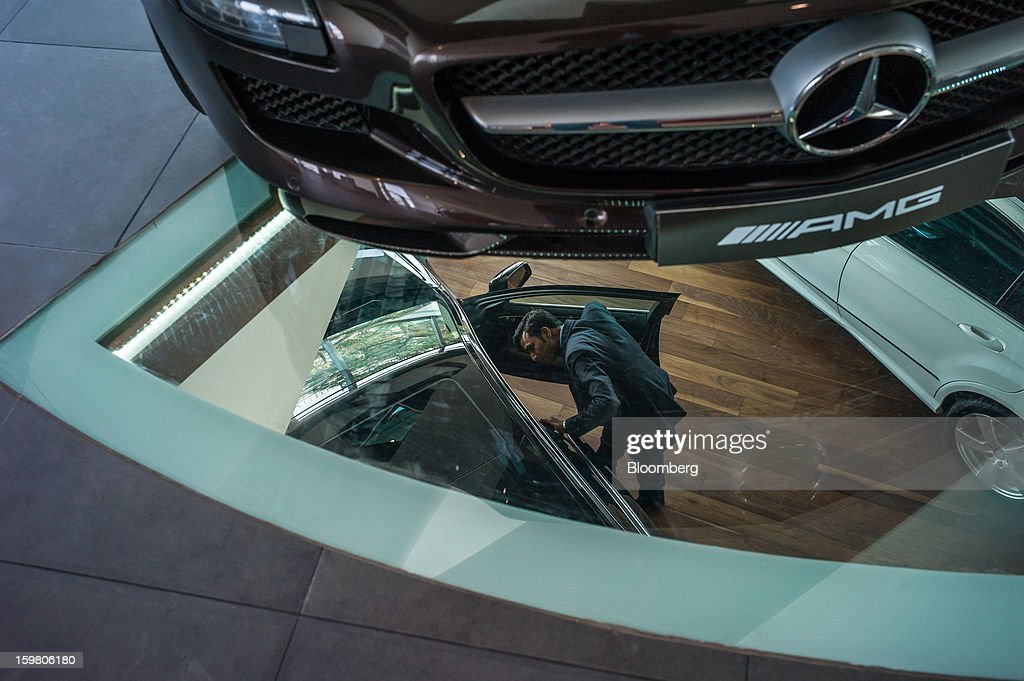A Daimler AG Mercedes-Benz SLS AMG Roadster vehicle sits on display as a T&T Motors Ltd. sales assistant is viewed through a glass floor talking to a customer inside the company's newly opened Mercedes-Benz India flagship dealership in New Delhi, India, on Saturday, Jan. 19, 2013. The Indian Finance Ministry projects Asia's third-largest economy will expand as little as 5.7 percent in the 12 months to March 31, which would be the weakest pace in a decade. Photographer: Sanjit Das/Bloomberg via Getty Images