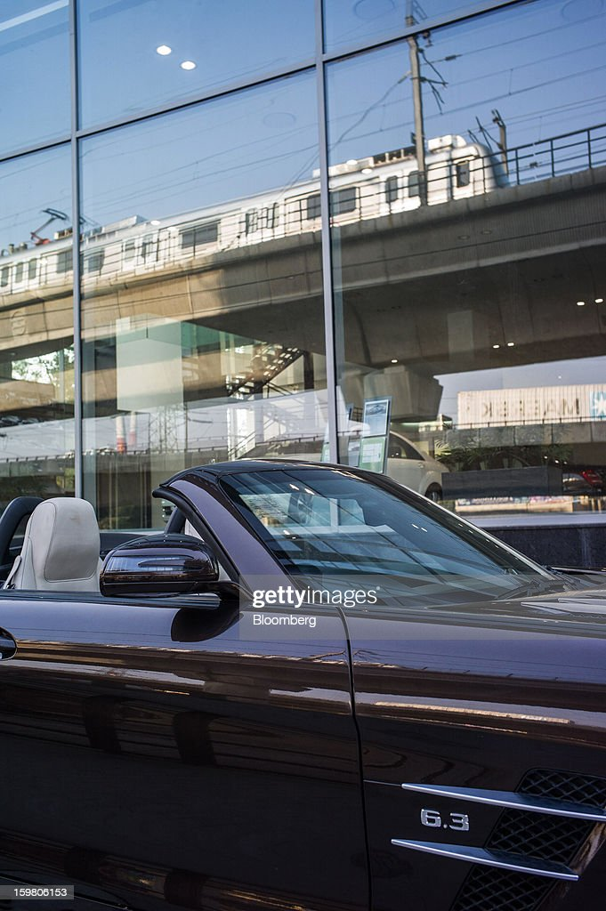 A Daimler AG Mercedes-Benz SLS AMG Roadster vehicle sits outside the newly opened T&T Motors Ltd. Mercedes-Benz India flagship dealership as a passing Delhi Metro Rail Corp. train is reflected in the dealership's window in New Delhi, India, on Saturday, Jan. 19, 2013. The Indian Finance Ministry projects Asia's third-largest economy will expand as little as 5.7 percent in the 12 months to March 31, which would be the weakest pace in a decade. Photographer: Sanjit Das/Bloomberg via Getty Images