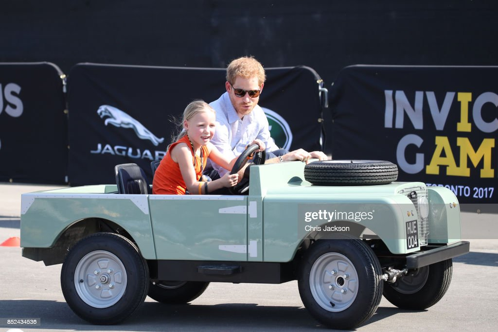 Daimy Gommers, 5, drives the car as Prince Harry rides beside her as he visits the Distillery District of the city for the Jaguar Land Rover driving challenge ahead of the Invictus Games 2017 on September 23, 2017 in Toronto, Canada
