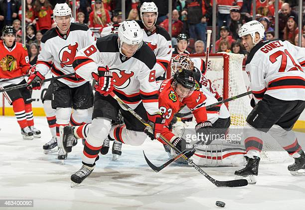 Dainius Zubrus of the New Jersey Devils and Kris Versteeg of the Chicago Blackhawks lunge for the puck during the NHL game at the United Center on...