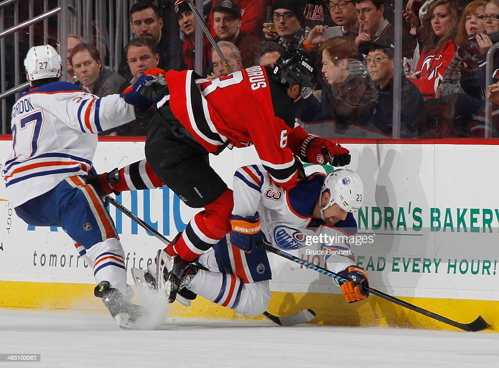 Dainius Zubrus of the New Jersey Devils and Matt Hendricks of the Edmonton Oilers collide along the boards during the third period at the Prudential...