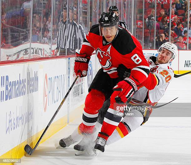 Dainius Zubrus of the New Jersey Devils battles for position against Curtis Glencross of the Calgary Flames at the Prudential Center on April 7 2014...