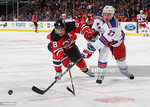 Dainius Zubrus of the New Jersey Devils battles hard for control of the puck against Ryan McDonagh of the New York Rangers during the game at the...