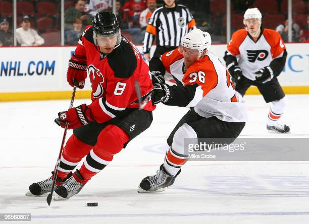 Dainius Zubrus of the New Jersey Devils carries the puck in front of Darrill Powe of the Philadelphia Flyers at the Prudential Center on February 10...