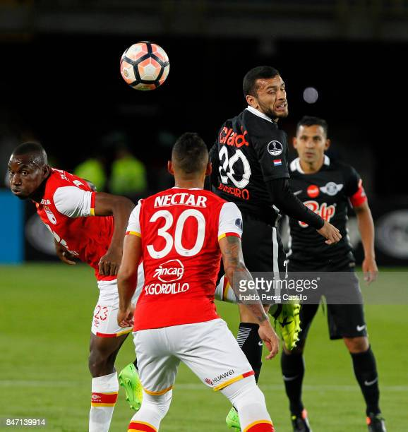 Dairon Mosquera and Yeison Gordillo of Santa Fe compete for the ball with Antonio Bareiro of Libertad during a second leg match between Independiente...