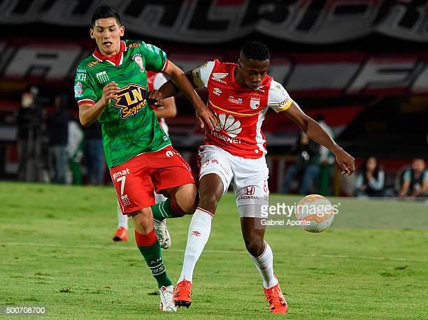 Dairon Mosquera of Santa Fe struggles for the ball with Cristian Espinoza of Huracan during a second leg final match between Independiente Santa Fe...