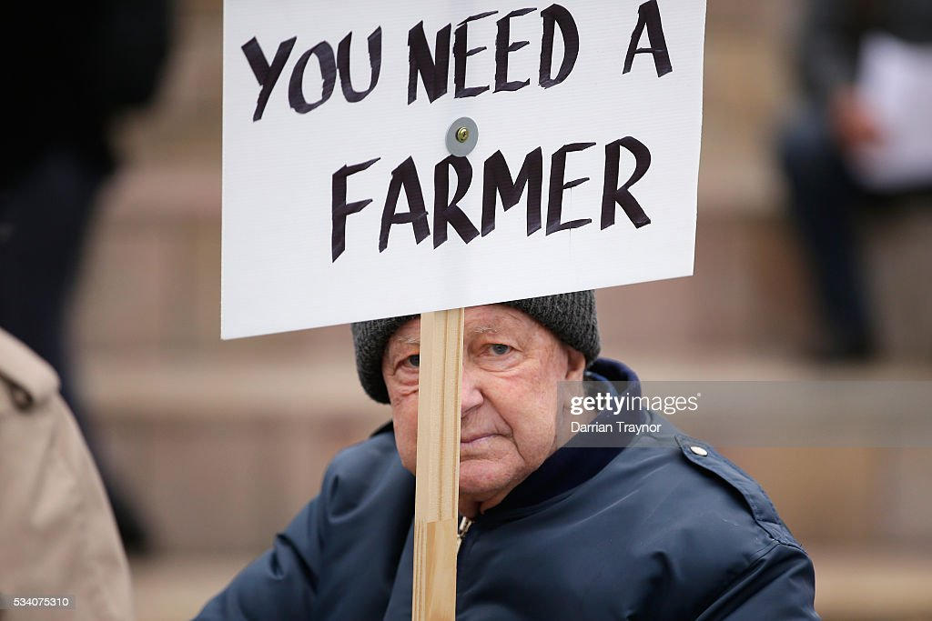 A Dairy Farmer holds up a placard during a march to Parliament House on May 25, 2016 in Melbourne, Australia. The Federal Government is expected to announce an assistance package for dairy farmers, who have been struggling due to falling milk prices in recent months.