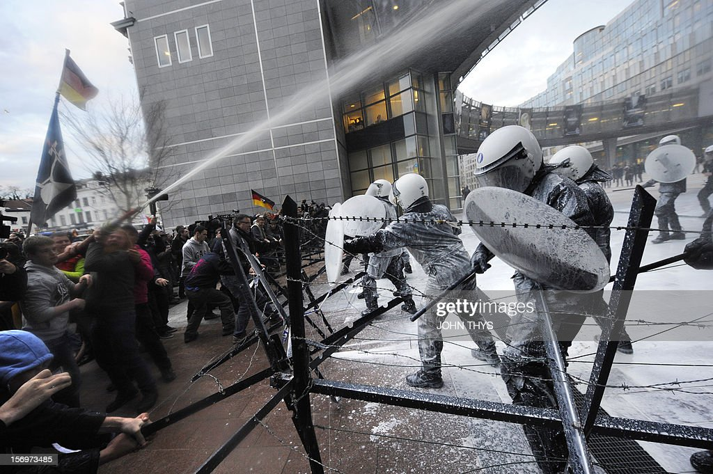 Dairy farmers spray milk to riot police during a protest against EU agricultural policies at the Place du Luxembourg, near the European Parliament, in Brussels, on November 26, 2012. Farmers demonstrated today with their tractors and fake cows at the European Parliament in Brussels to protest against falling milk prices caused by overproduction in Europe. AFP PHOTO / on November 26, 2012. AFP PHOTO / JOHN THYS