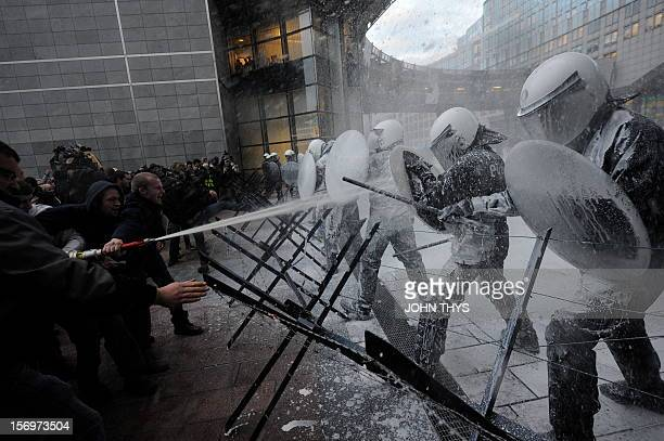 Dairy farmers spray milk to riot police during a protest against EU agricultural policies at the Place du Luxembourg near the European Parliament in...