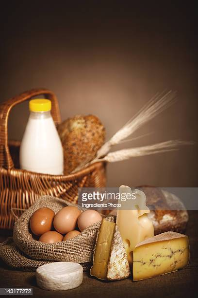 Dairy products, bread and eggs on linen canvas.
