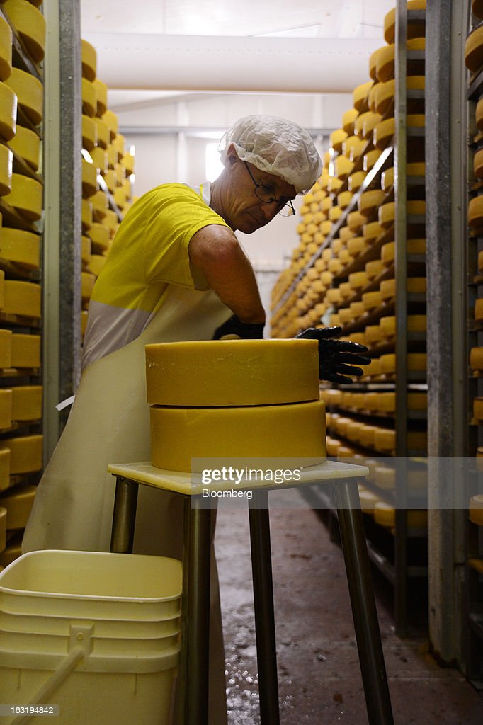 A dairy worker washes the rind on a wheel of hard cheese in the maturing room at the Tasmanian Heritage cheese plant, operated by Kirin Holdings Co.'s Lion unit, in Burnie, Tasmania, Australia, on Monday, Feb. 25, 2013. Australia's economy expanded in 2012 at the fastest pace in five years as resource investment and exports outweighed subdued manufacturing and construction. Photographer: Carla Gottgens/Bloomberg via Getty Images