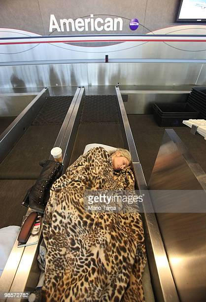 Daisia Garvilova of Russia stranded since April 15 sleeps on a baggage belt inside John F Kennedy International Airport while hoping to catch a...