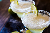 two frozen margaritas with lime and salt