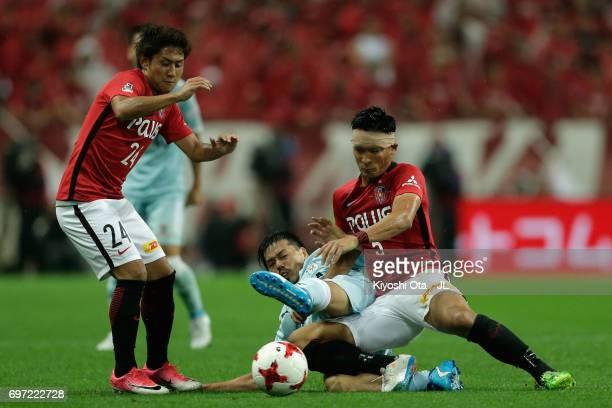 Daisuke Matsui of Jubilo Iwata competes for the ball against Takahiro Sekine and Tomoaki Makino of Urawa Red Diamonds during the JLeague J1 match...
