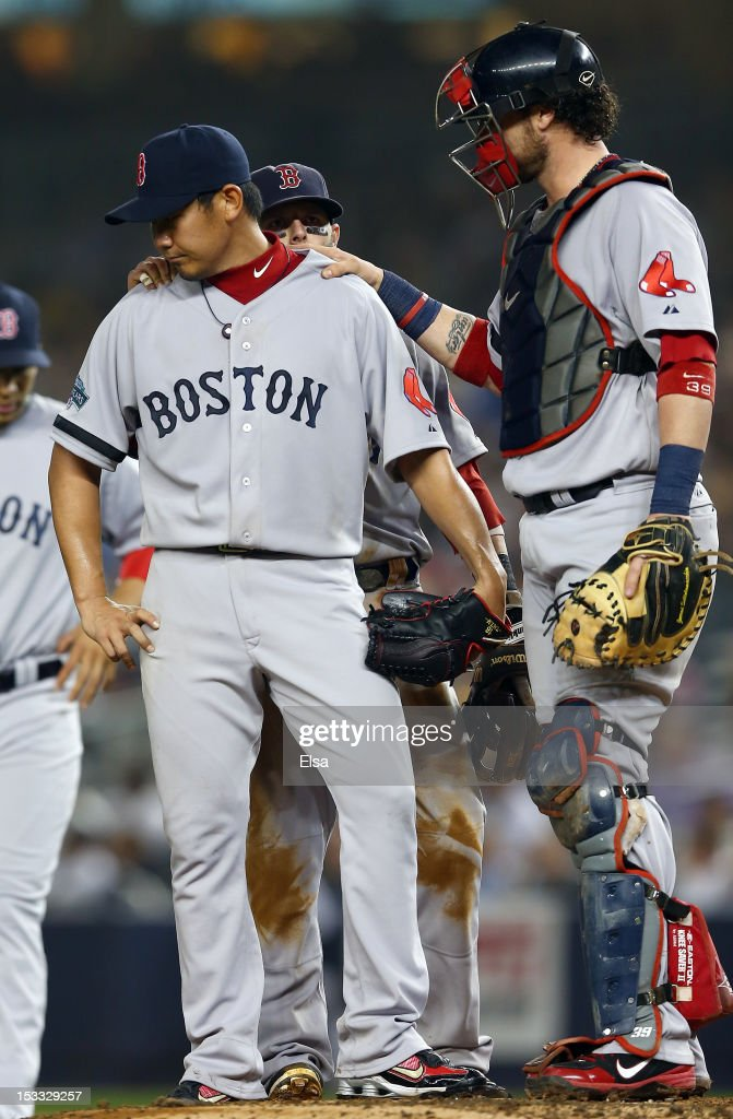 Daisuke Matsuzaka #18 of the Boston Red Sox is consoled by teammate Jarrod Saltalamacchia #39 as Matsuzaka is about to be taken out of the game against the New York Yankees on October 3, 2012 at Yankee Stadium in the Bronx borough of New York City.