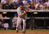 Daisuke Matsuzaka of the New York Mets attempts to bunt against relief pitcher Rex Brothers of the Colorado Rockies in the seventh inning at Coors...