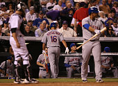 Daisuke Matsuzaka of the New York Mets returns to the dugout after striking out bunting against relief pitcher Rex Brothers of the Colorado Rockies...