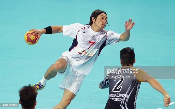 Daisuke Miyazaki of Japan is defended by Ho Wai Kit of Hong Kong during the Handball Men's Group G match between Hong Kong and Japan during the 2014...