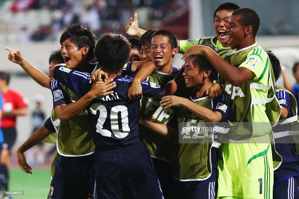 Daisuke Sakai (front) of Japan celebrates his team's first goal with team mates during the FIFA U-17 World Cup UAE 2013 Group D match between Japan and Tunisia at Sharjah Stadium on October 24, 2013 in Sharjah, United Arab Emirates.