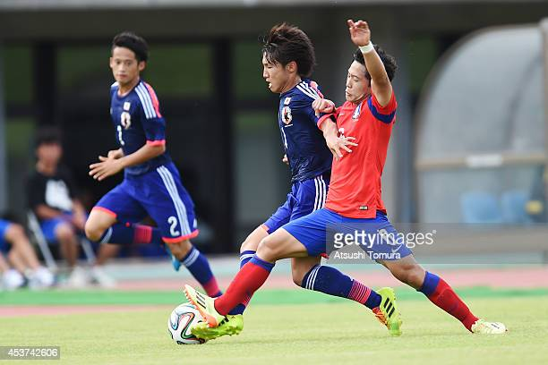 Daisuke Sakai of Japan is challenged by Hyeonug Kim of South Korea in the U19 match between South Korea and Japan during SBS Cup International Youth...