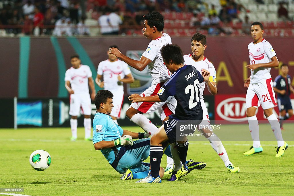 Daisuke Sakai of Japan scores his team's first goal against goalkeeper Hamza Ben Chrifia of Tunisia during the FIFA U-17 World Cup UAE 2013 Group D match between Japan and Tunisia at Sharjah Stadium on October 24, 2013 in Sharjah, United Arab Emirates.
